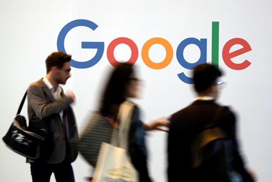 Googleロゴの前を通り過ぎる人々。
