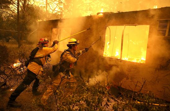 炎が燃え広がることを防ぐ消防士