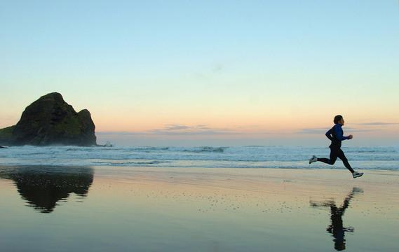 朝のルーティン:海辺を走る男性