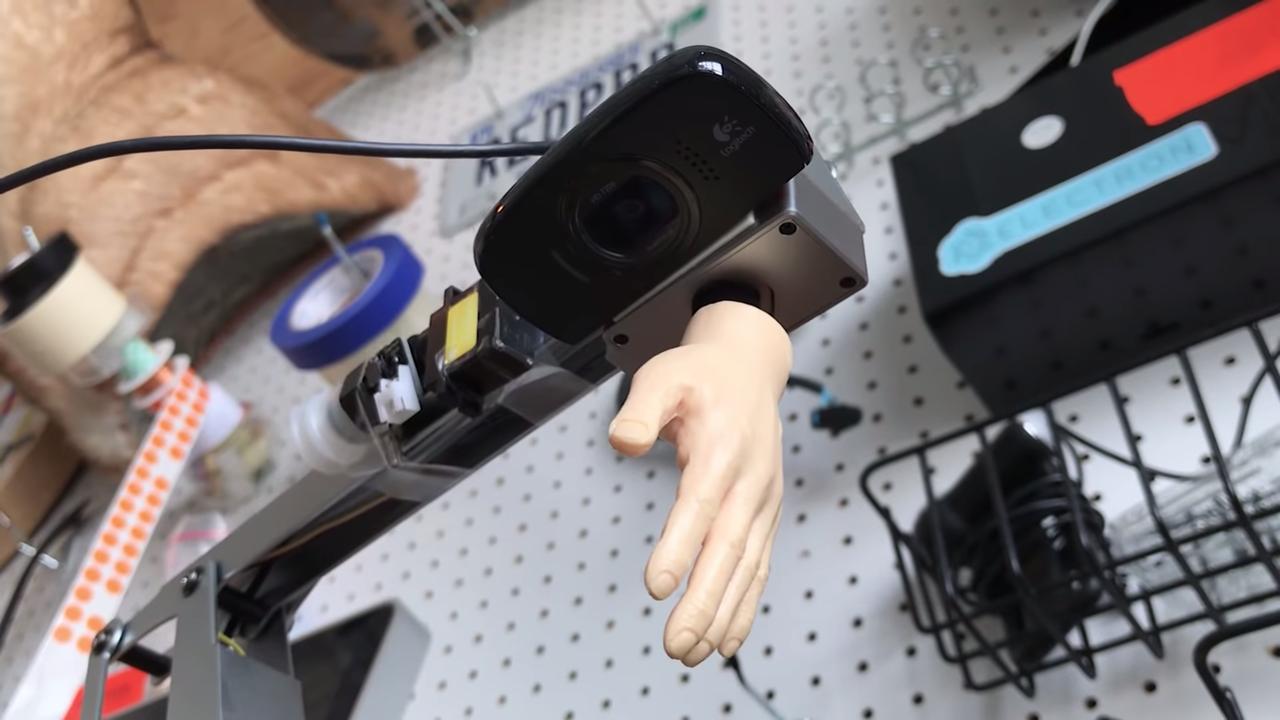ラズベリーパイ(Raspberry Pi)で制御されているロボットアームは、パイソン(Python)でプログラミングされ、アームを伸ばして「ウォーリーをさがせ!」のページの写真を撮る。