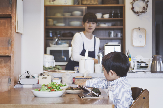 息子を見ながら食事を作る主婦