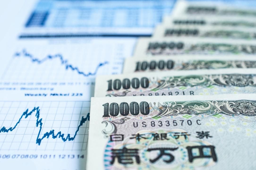 1万円札と経済指標のグラフ。