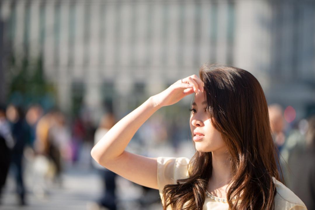 強い日射しの下で眩しそうにしている女性