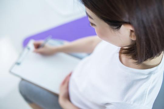 運動記録を書く妊婦