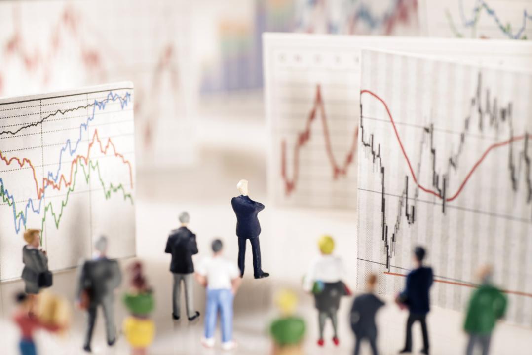 株価チャートを見る人たち。