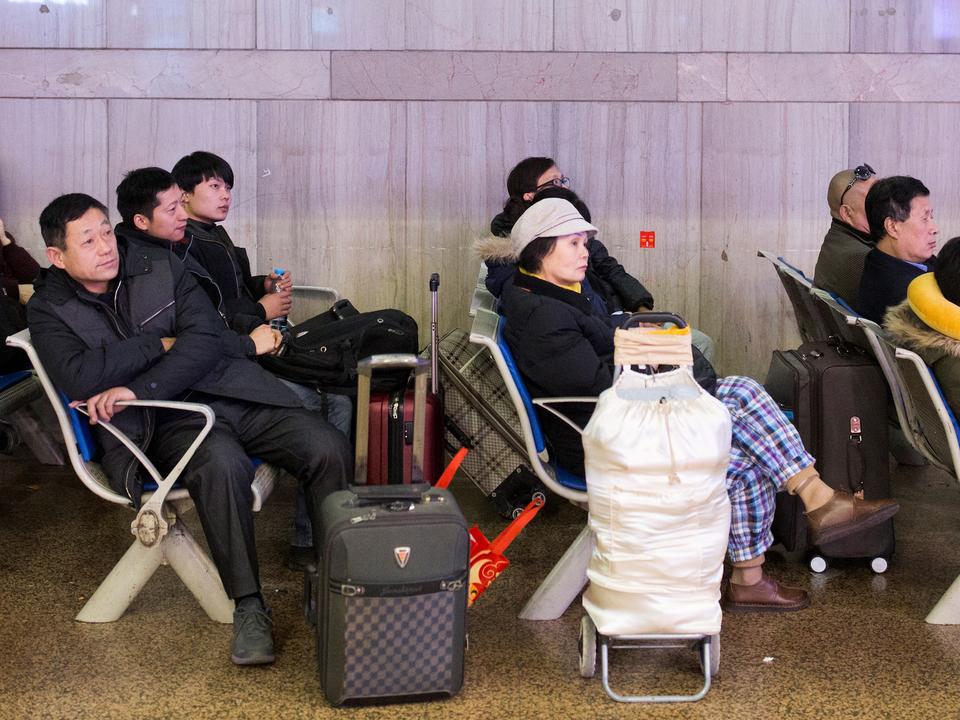 空港でテレビを見る人々