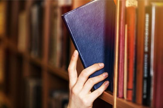本棚から一冊手をだしている様子