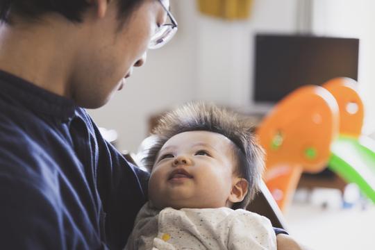 赤ん坊を抱く男性。
