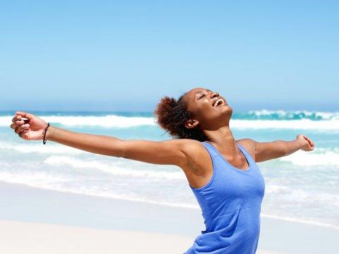 笑顔で日光浴をする女性