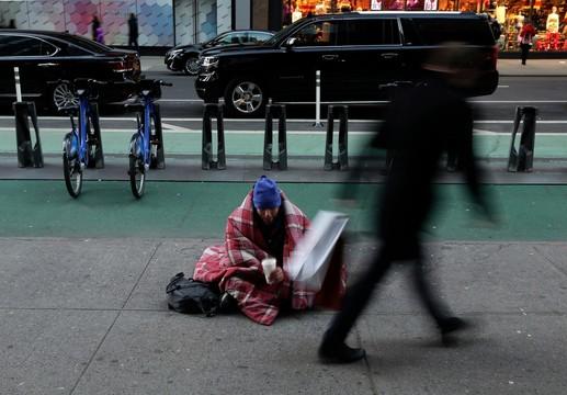 歩行者がカップに入れてくれたお金を確認するホームレスの男性。