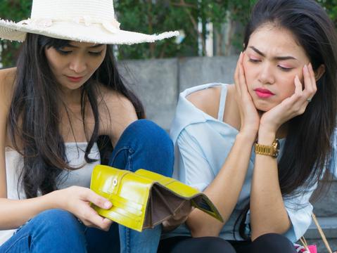 からっぽのお財布を見る2人の女性