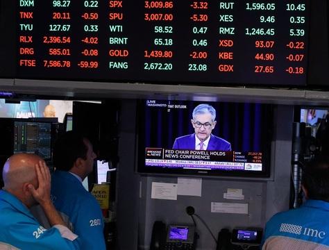 ニューヨーク証券取引所でパウエルFRB議長の記者会見を見守るトレーダーたち。