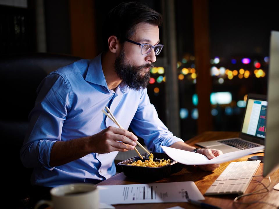 働きながら食事をとる男性