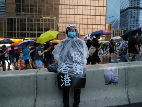 8月18日、香港で行われたデモ行進中、レインコートを着た参加者が「香港を守れ」と書かれたプラカードをつけている。