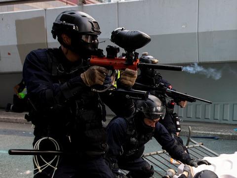 香港の立法会総合ビル近くでデモ参加者に向けて催涙スプレーを発射する警官。2019年9月29日。