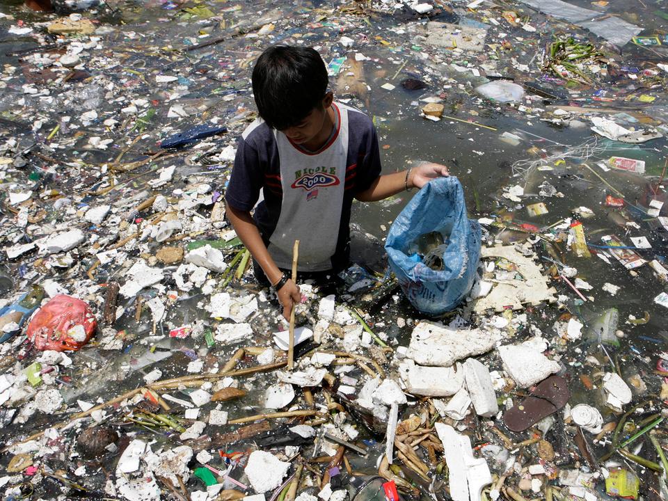 フィリピンの汚染された沿岸部で、プラスチックを集める少年。