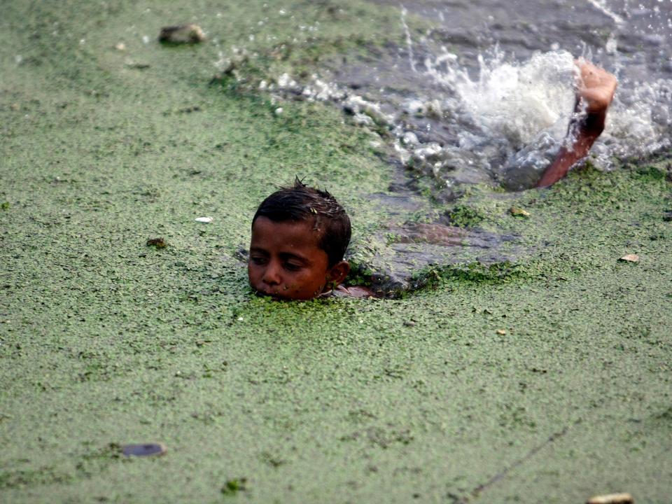 汚染されたブリゴンガ川で泳ぐ少年。ダッカ、バングラデシュ。2009年5月。