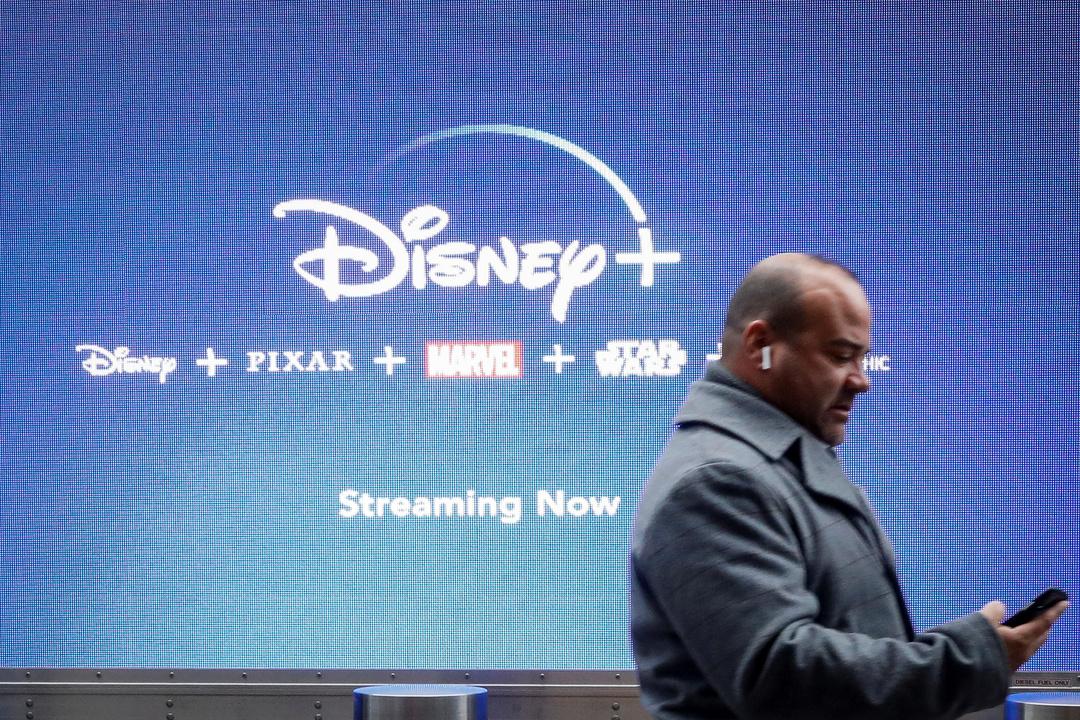 Disney+の広告の前を歩く男性