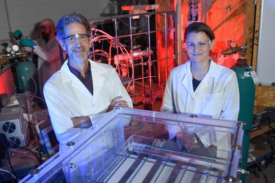 プラズマリアクターのそばに立つクラークソン大学のトム・ホルセン教授とセルマ・メディドビック教授。