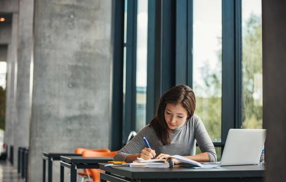 机に座って勉強する女性