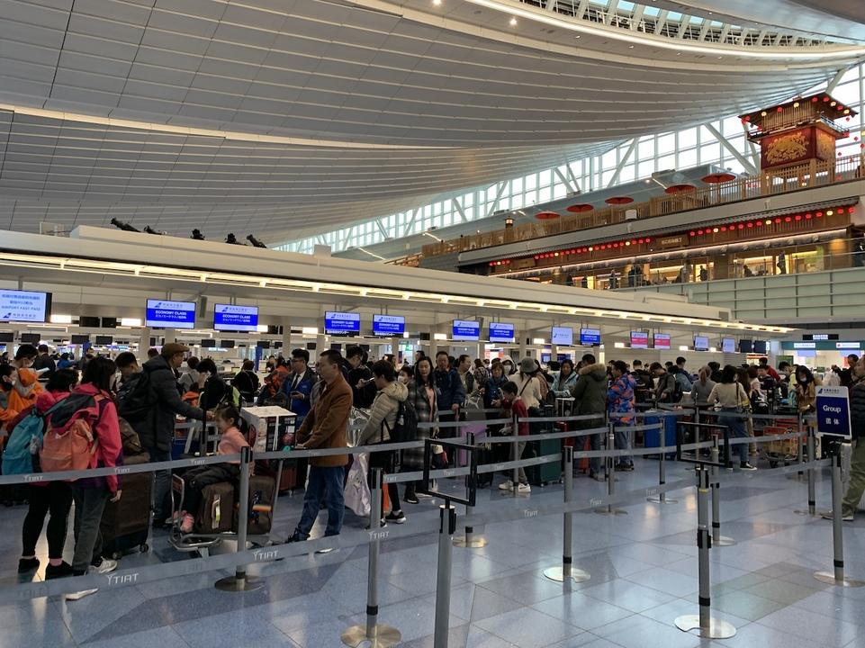羽田空港でチェックインを待つ人々。春節のため、多くの中国人旅行客が帰省の途につく。