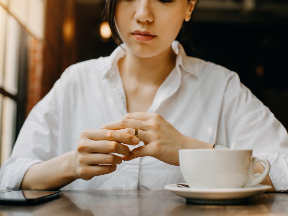 結婚指輪を見つめる女性