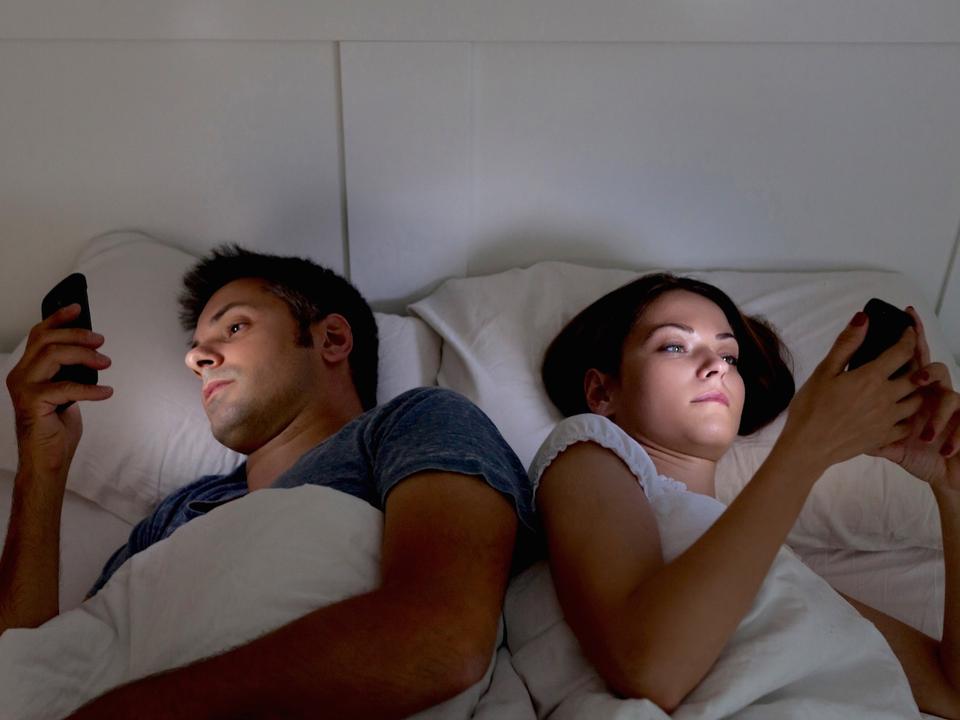 ベッドで携帯電話をいじるカップル