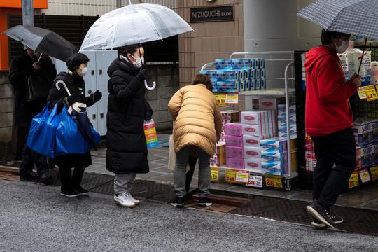 ドラッグストアで日用品を買う人々。