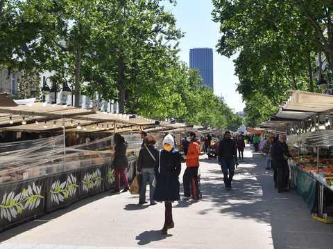 トゥール・モンパルナスの隣にあるサックス・ブルトゥイユ市場を、マスクをつけて通り過ぎるパリ市民。2020年5月14日。
