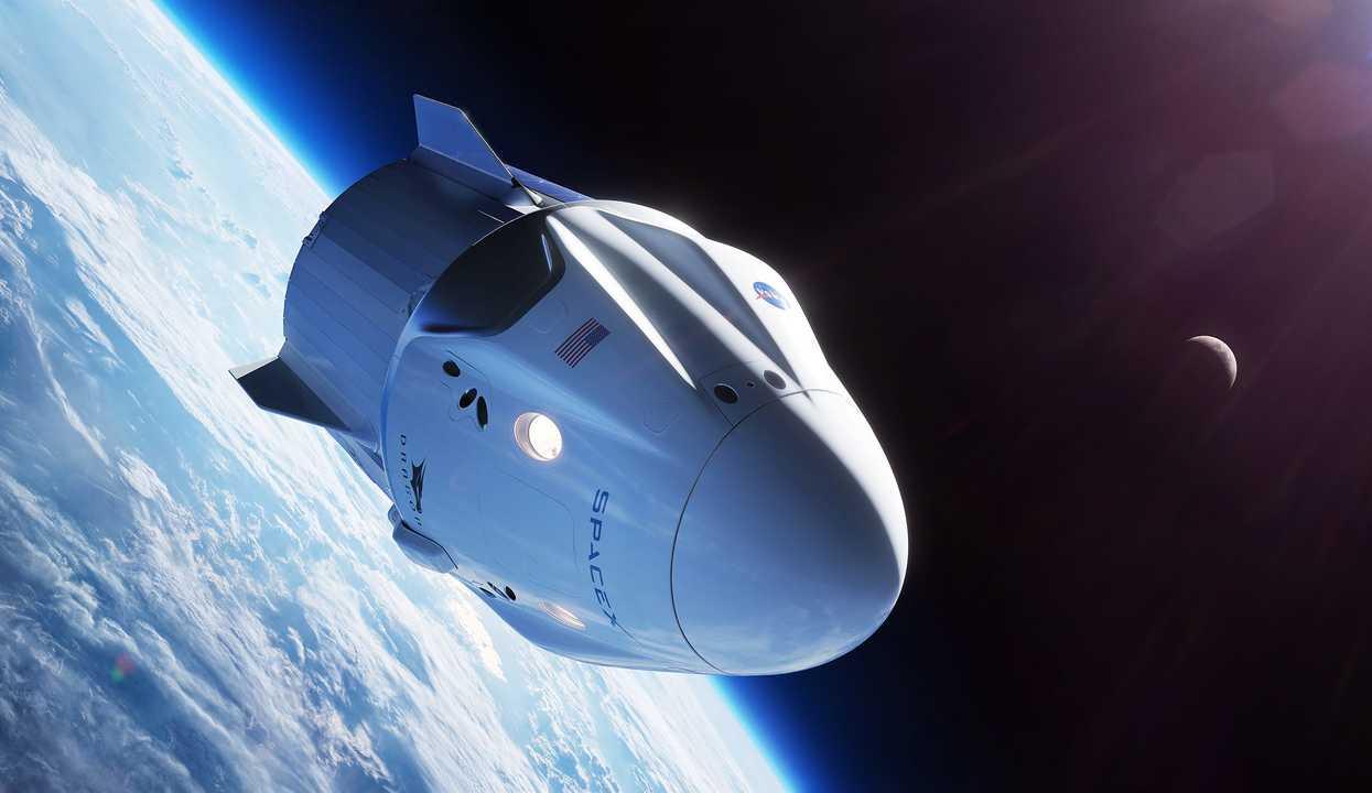 地球を周回するスペースXのクルードラゴンのイラスト。ドラゴン2、またはドラゴンV2とも呼ばれる。最初のドラゴンは、人を運ぶように設計されていなかった。