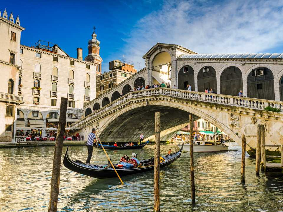 ヴェネツィアの夕暮れ時。リアルト橋(Ponte di Rialto)の下をゴンドラが通る。