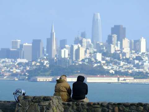 サンフランシスコのスカイラインを望む展望台に座るカップル。