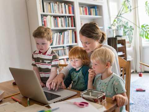 子どもと一緒にパソコンを使う女性