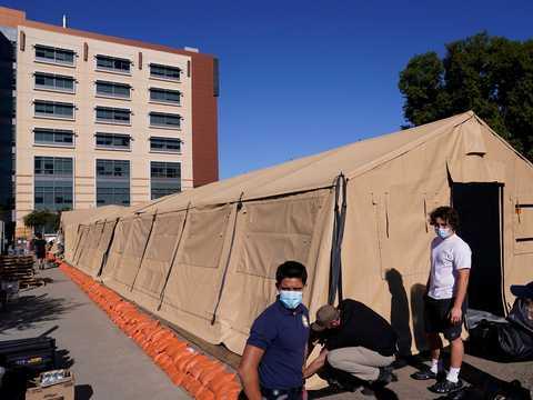 2020年12月21日、カリフォルニア州オレンジ郡のUCI医療センターが設置した簡易病棟の外に立つエンジニアとボランティア。