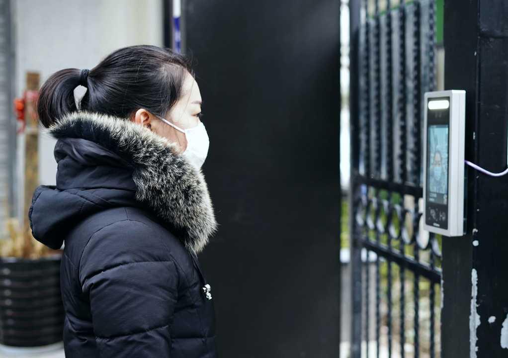 2020年3月3日、新型コロナウイルスが大流行する中、住居に入るために顔認証システムの前に立つマスクをつけた女性。