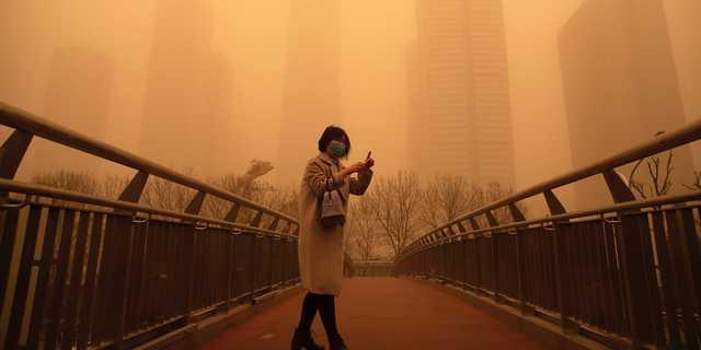 2021年3月15日、北京の朝の通勤時間帯に歩道橋を歩く女性。