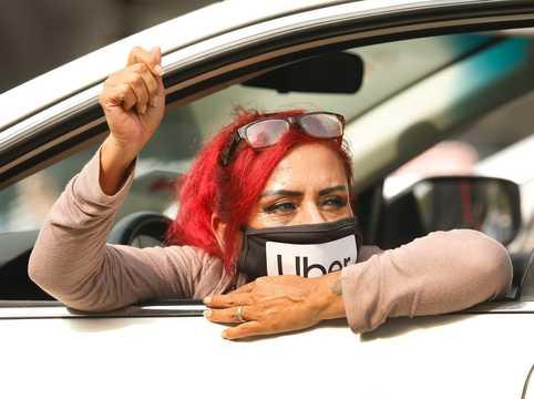 ライドシェアドライバーのテレサ・メルカードさんが拳を上げて訴える。2020年10月8日、配車サービスのギグワーカーが、ロサンゼルス市庁舎前の道路を車で塞ぎ、デモを行った。