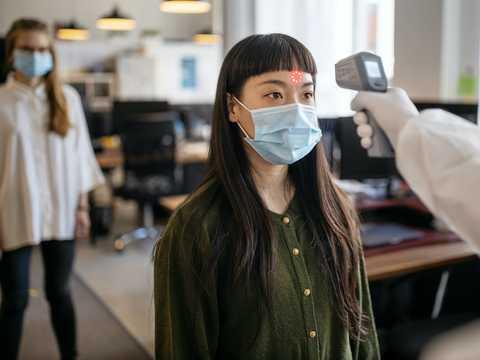 出勤前に体温を測定しているマスク姿の女性