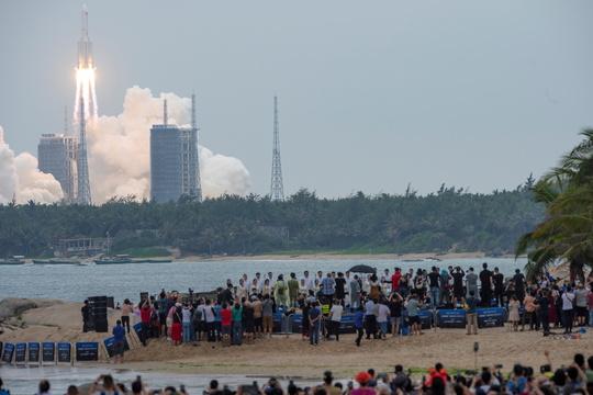 4月29日、中国南部の文昌衛星発射センターから発射された長征5号Bロケットを眺める人々。