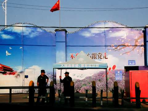 Security guards stand at the gates of what is officially known as a vocational skills education centre in Huocheng County.
