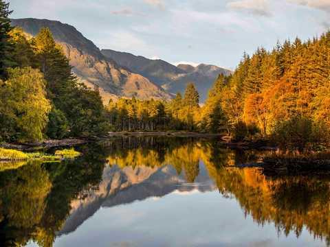 スコットランド・ハイランド地方のグレンコー・ローチャンの静かな水面に映る紅葉した木々。ここがウルトラマラソンのスタート地点となる。