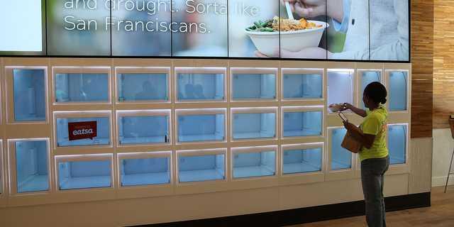 2015年8月31日、サンフランシスコにある全自動ファストフード店イーツァ(eatsa)でピックアップロッカーからランチを受け取る客。