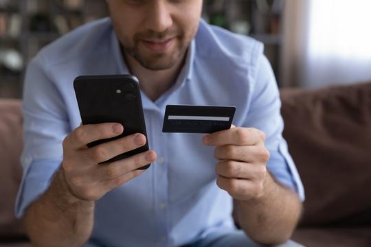 クレジットカードを見るミレニアル男性