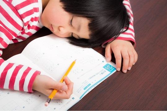 宿題をしながら寝る子ども