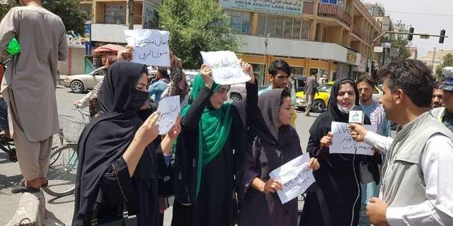 大統領官邸の前で権利保護を求めてプラカードを掲げるアフガニスタンの女性。