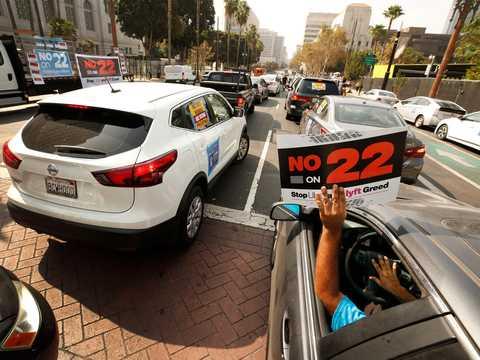 Rideshare driver Jorge Vargas raises his No on 22 sign