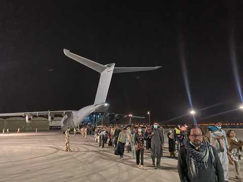 カブール空港から退避する人々。