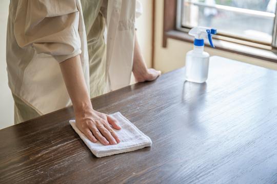 机を拭く女性。