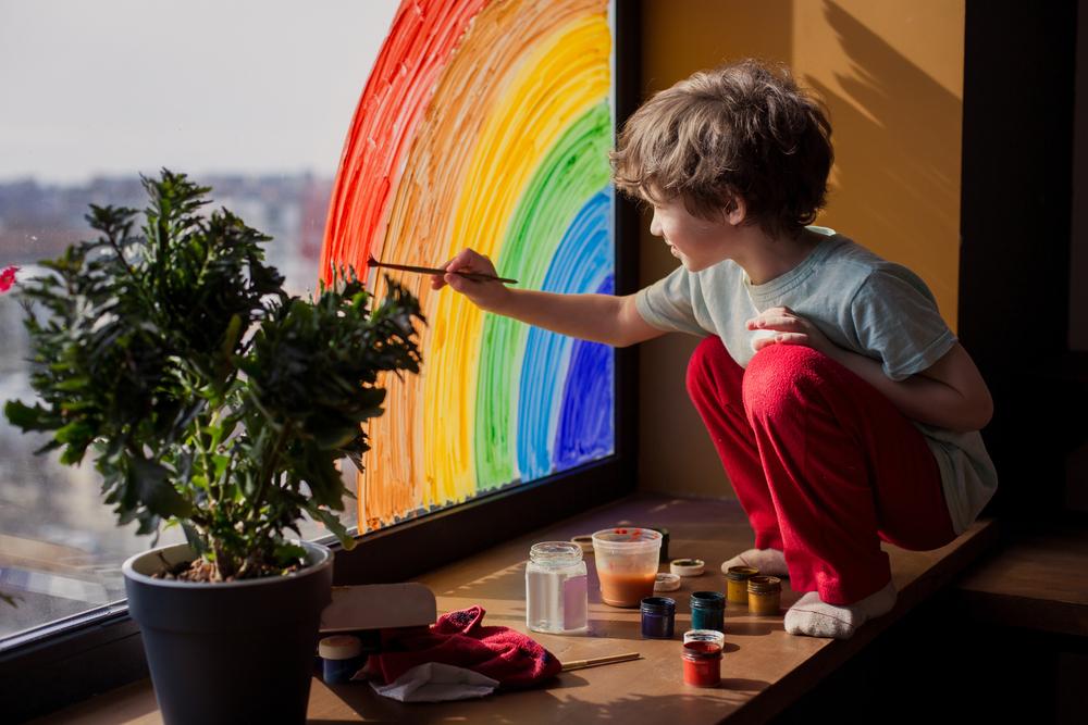 窓に虹を描く子ども