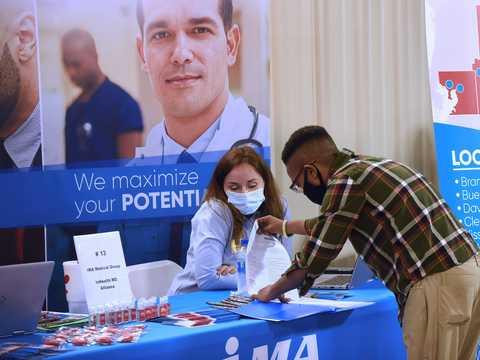 フロリダ州フェアグラウンドで開催された就職フェアで、履歴書を差し出す男性。